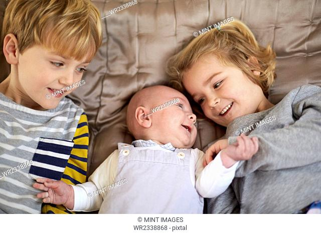 Three children lying on a bed, a boy and girl with a baby between them