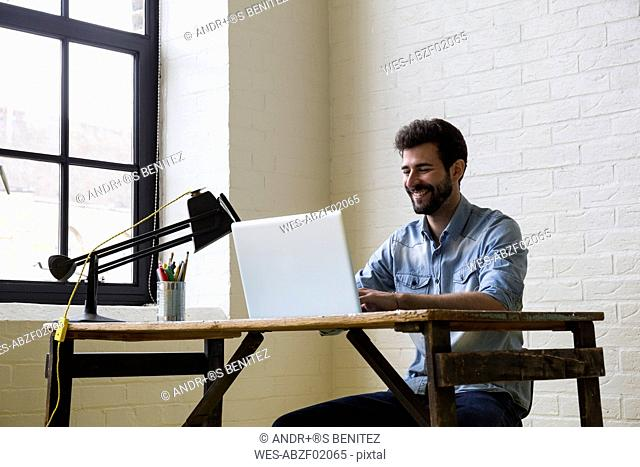 Smiling man woking at desk with laptop
