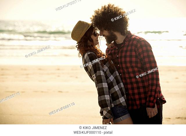 Spain, Cadiz, young couple in love standing face to face on the beach