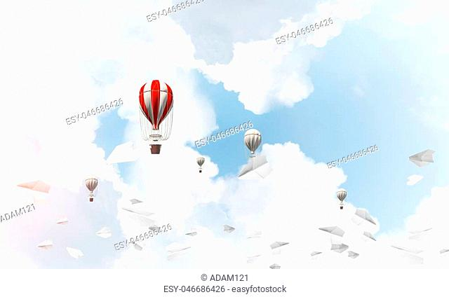 Colorful aerostats flying among paper planes and over the blue cloudy sky. 3D rendering