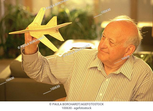 Senior man with toy airplane