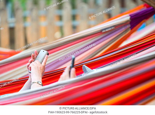 22 June 2019, Rhineland-Palatinate, Mainz: A woman lies on the banks of the Rhine in a hammock and operates her smartphone. Photo: Andreas Arnold/dpa