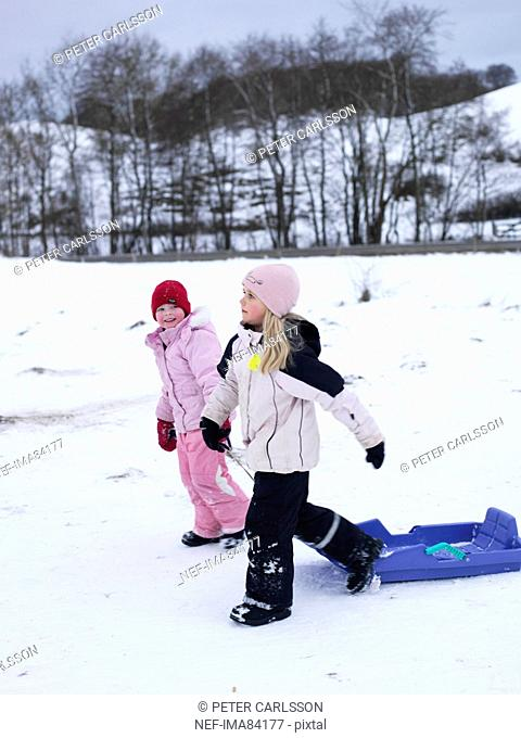 Two children dragging toboggan, walking