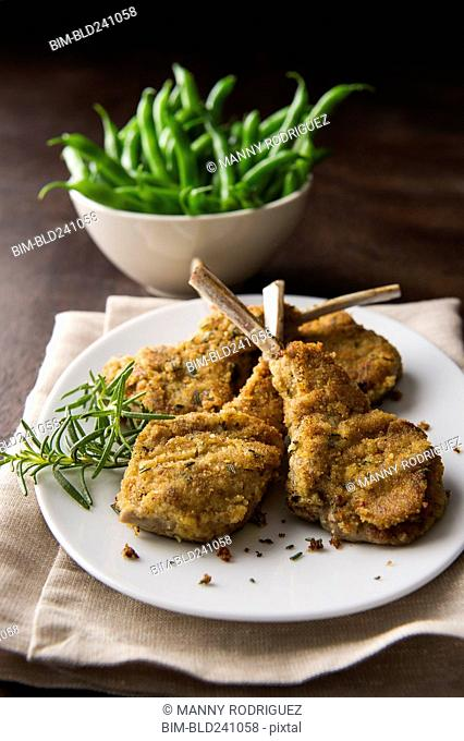 Breaded lamb chops on plate with bowl of green beans