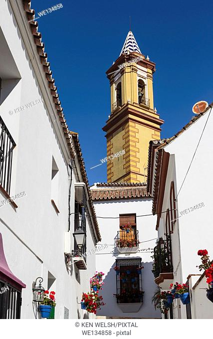 Estepona, Costa del Sol, Malaga Province, Andalusia, southern Spain. Church. Tower of Iglesia de Nuestra Señora de los Remedios church seen at end of Calle...
