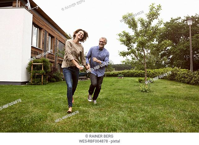 Happy mature couple running in garden
