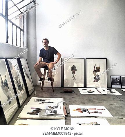 Artist sitting with work in gallery