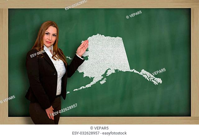 Successful, beautiful and confident young woman showing map of alaska on blackboard for presentation, marketing research and tourist advertising