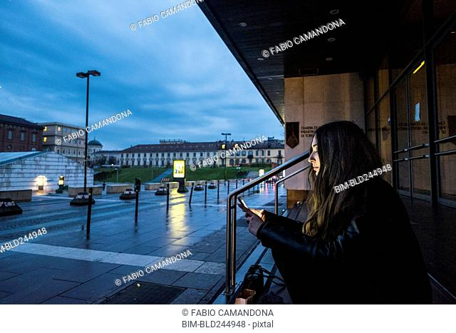 Caucasian woman sitting on staircase outdoors texting on cell phone