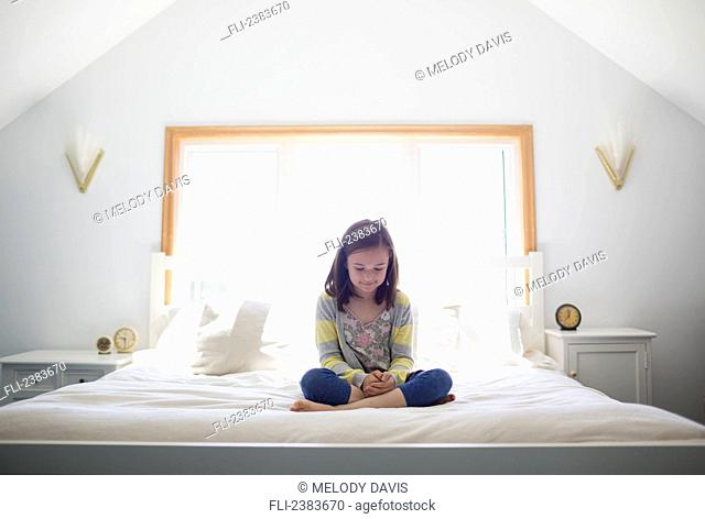 Young girl sitting cross-legged on her bed; Victoria, Vancouver Island, British Columbia, Canada