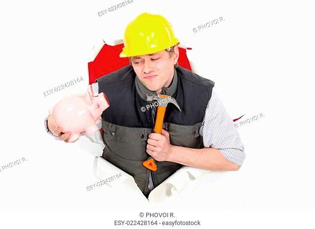 Laborer holding hammer and piggy bank