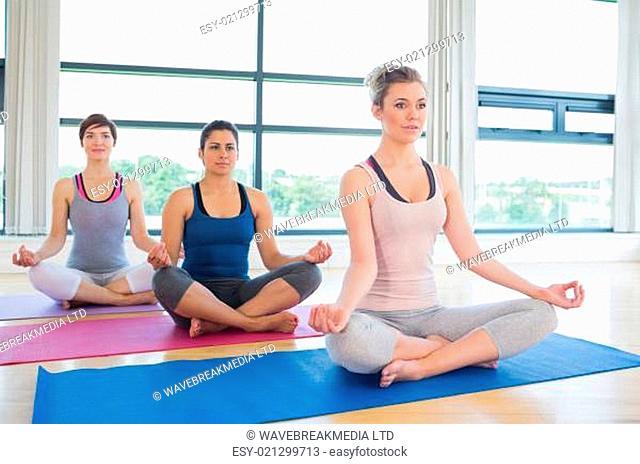 Women meditating in easy yoga pose in fitness studio