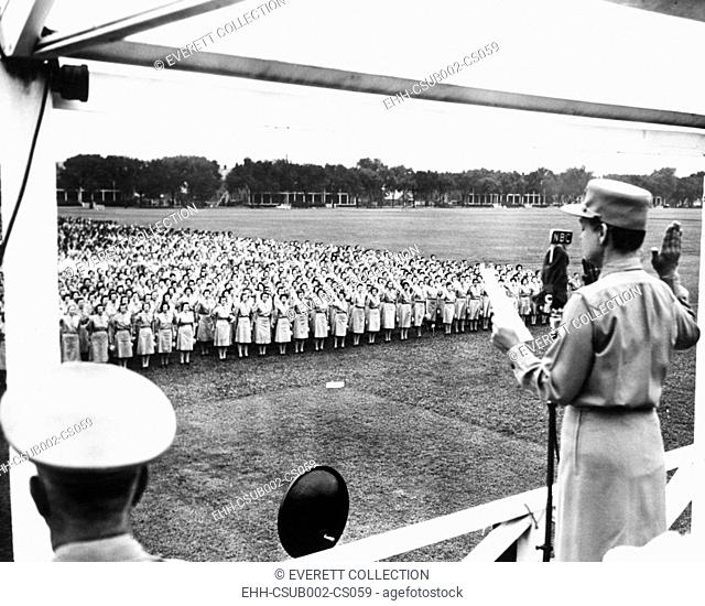 Col. Oveta Culp Hobby administering the Army oath to several thousand women. Aug. 5, 1943. They were in newly named, 'Women's Army Corps