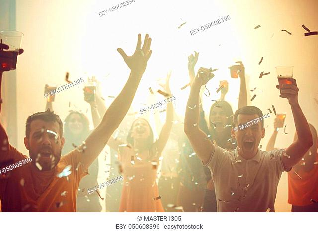 Nightlife and disco concept. Young people are dancing in club or outdoor in sunlight. Happiness, holidays, youth concepts