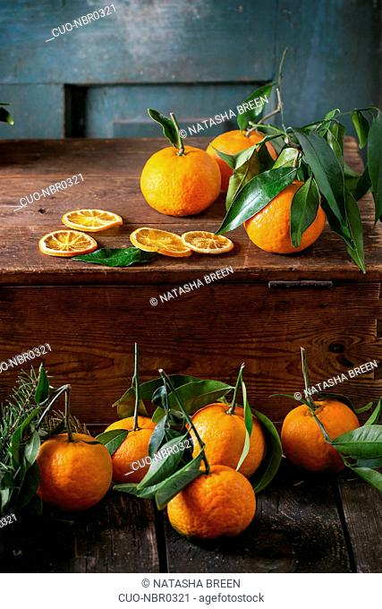 Tangerines with leaves in Christmas decor with Christmas tree and dry orange on wooden chest over old wooden table. Dark rustic style
