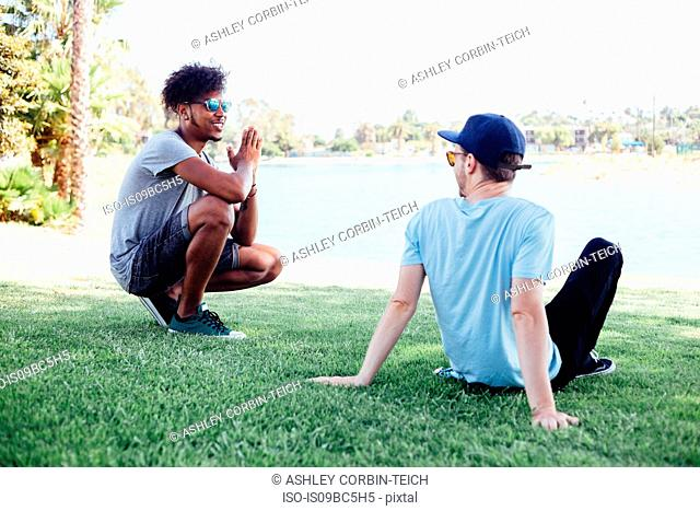 Friends relaxing on grass by lake, Long Beach, California, US