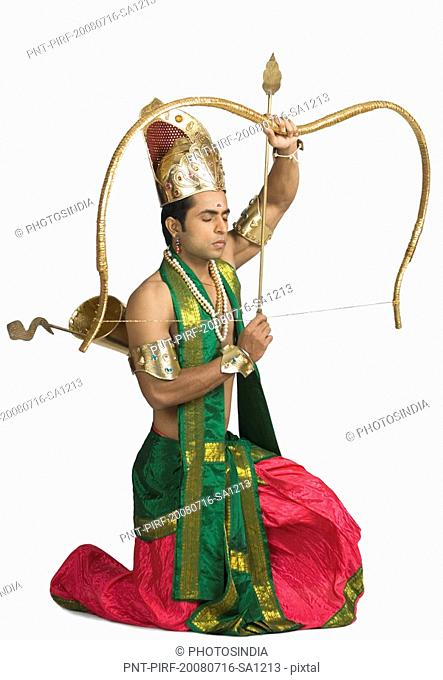 Young man in a character of Arjuna and holding a bow and arrow