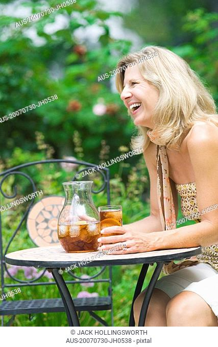 Side profile of a mature woman sitting at a table and drinking ice tea