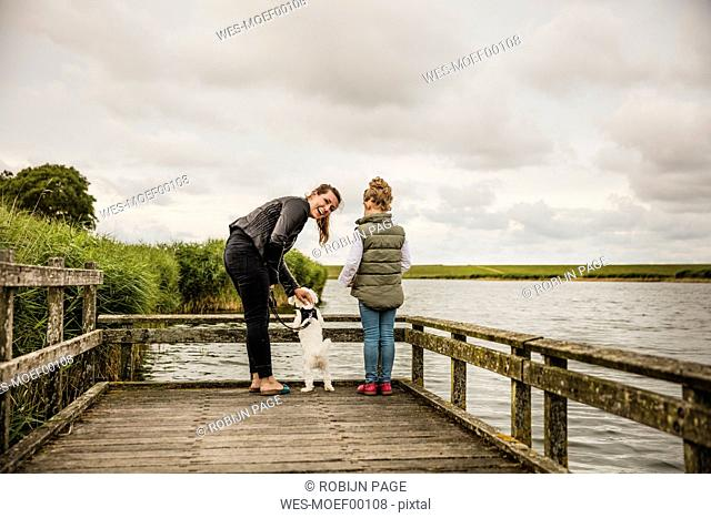 Mother and daughter standing on jetty at a lake with dog