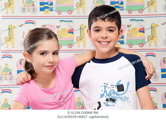 Portrait of a boy and girl smiling with arm around