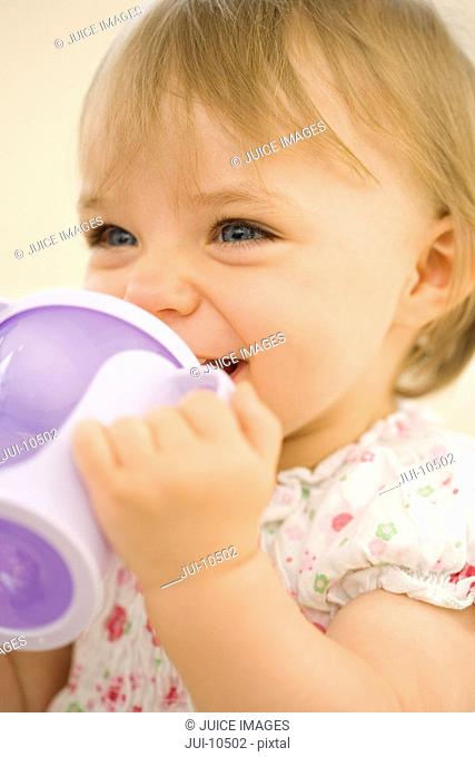 Baby girl 9-12 months drinking from baby cup, smiling, close-up