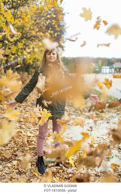 Playful tween girl playing in autumn leaves in park