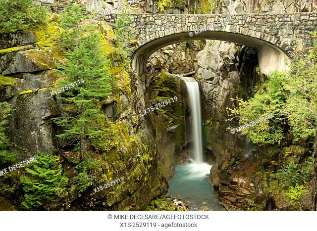 Christine Waterfall in Mt. Rainier National Park is framed by a stone bridge and rock cliffs