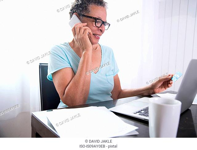 Senior woman sitting at table, using laptop, paperwork on table
