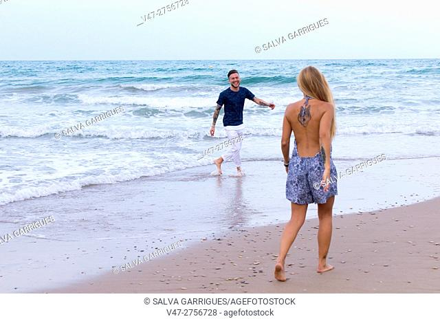 Young couple playing on the beach of Saler, Valencia, Spain, Europe
