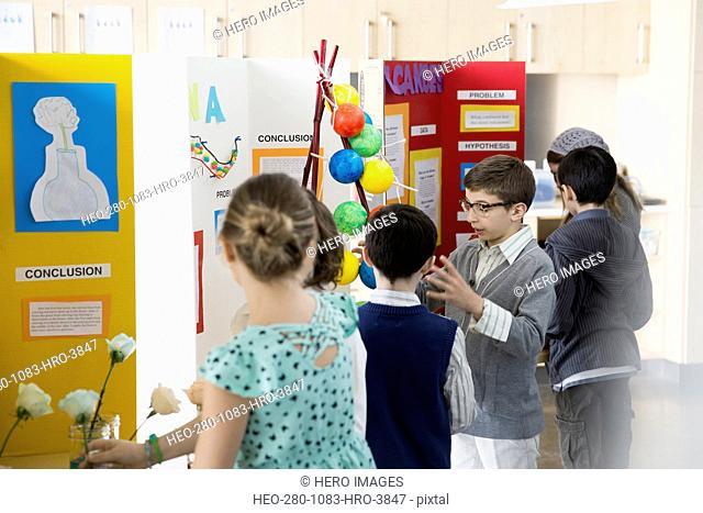 School boy explaining science fair project to classmates