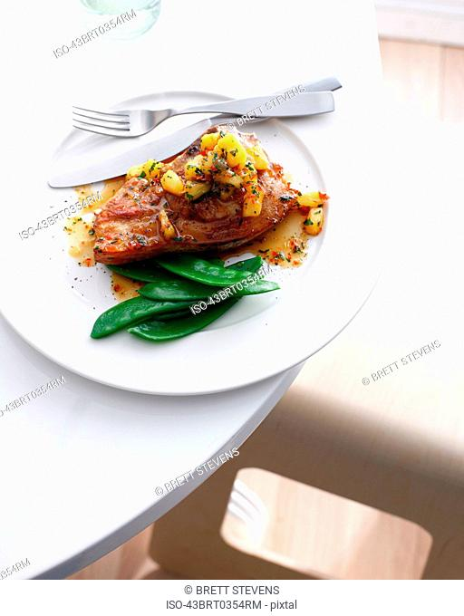Plate of pork with pineapple and beans