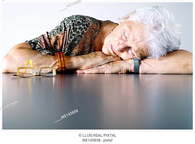 portrait of elderly woman with white hair, sleeping leaning on a table