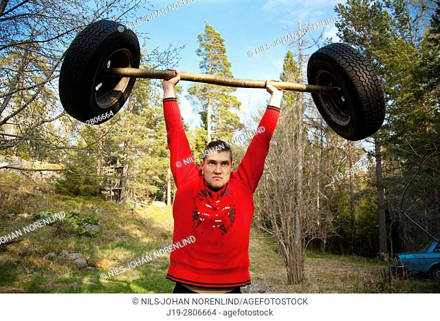 Man weightlifting in nature with homemade barbell, swedish archipelago