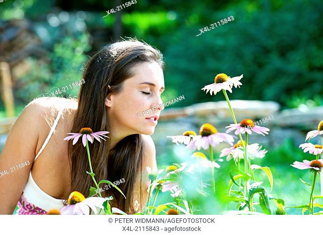 Young, beautiful woman in garden, Echinacea purpurea (model-released)