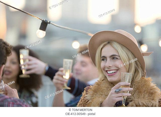 Smiling young woman drinking champagne at party