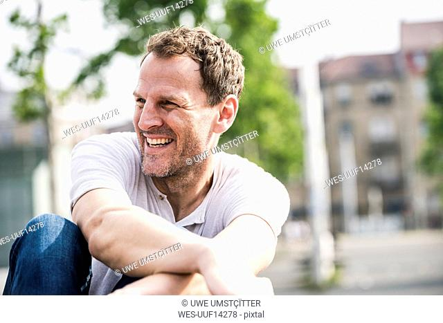 Laughing man sitting outdoors