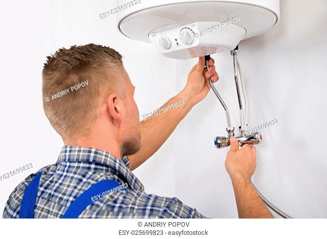 Young Male Worker Fixing Electric Boiler With Screwdriver