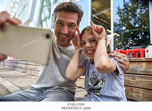 Father and playful daughter taking a selfie at an outdoor cafe
