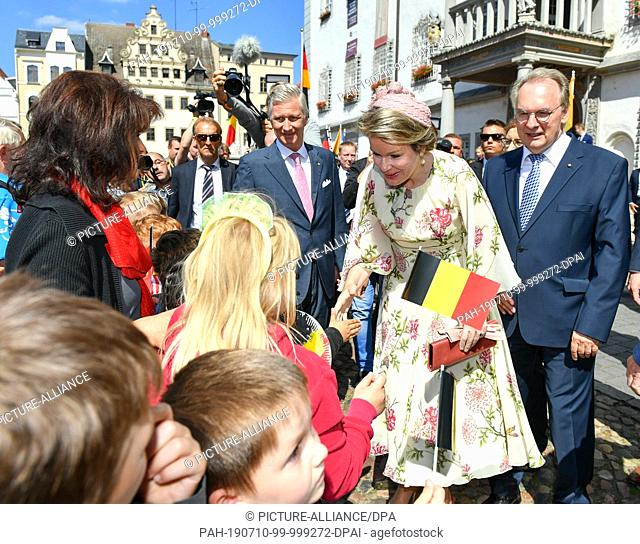 10 July 2019, Saxony-Anhalt, Wittenberg: The Belgian royal couple King Philippe and Queen Mathilde are greeted by onlookers and children with Belgian flags