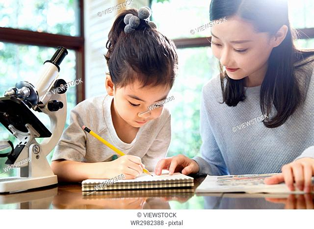 Mother helping daughter study