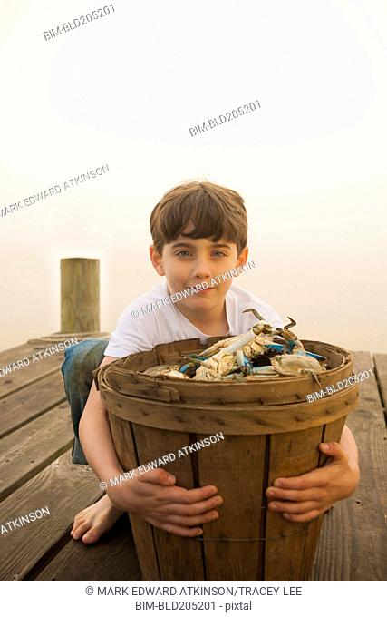 Caucasian boy holding basket of crabs