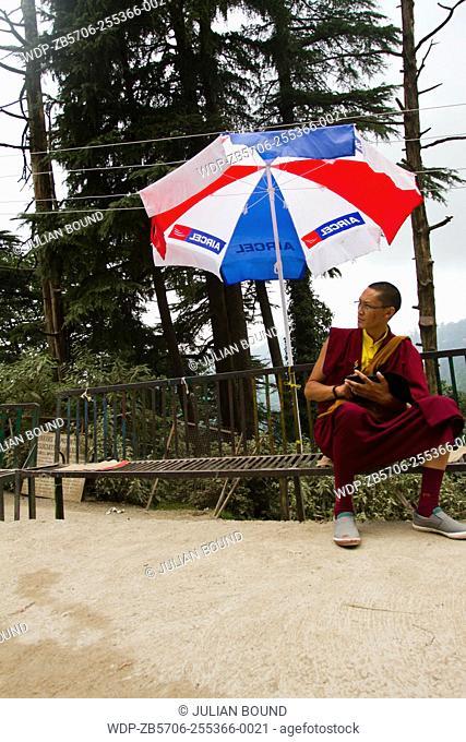 A young Tibetan Buddhist monk sits under an umbrella in Mcleod Ganj, India