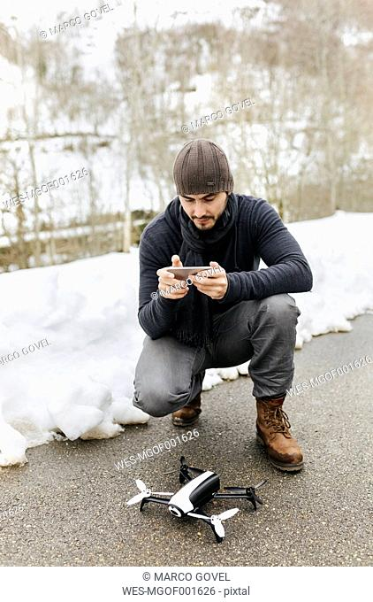 Spain, Asturias, man with telecontrol and drone in winter