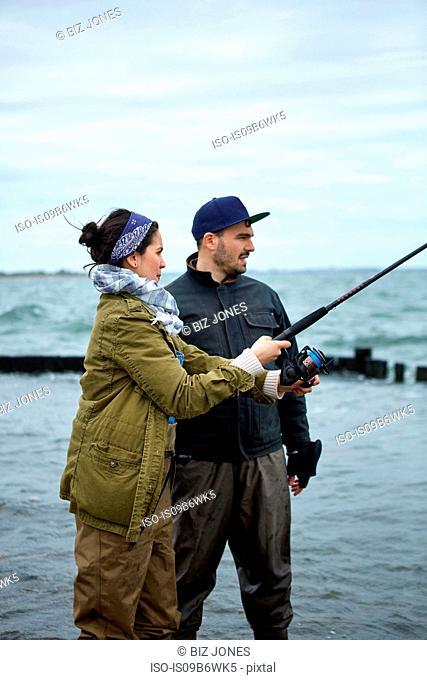 Young man teaching girlfriend sea fishing in sea