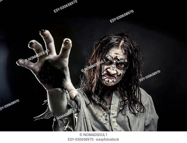 Horror zombie woman with bloody face reaching hand to you