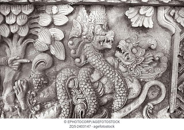 Singaraja temple, A demon being attacked by a Dragon.- on the entrance facet of the temple. Bali Indonesia