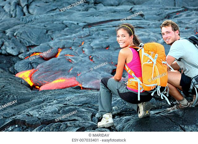 Hawaii lava tourist on hike. Tourists hiking near flowing lava from Kilauea volcano around Hawaii volcanoes national park, USA. Multiethnic couple