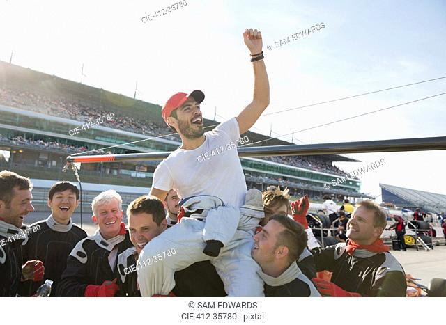 Formula one racing team carrying cheering driver on shoulders, celebrating victory on sports track