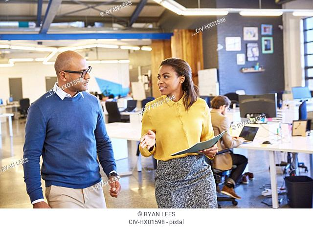Businessman and businesswoman walking and talking in office