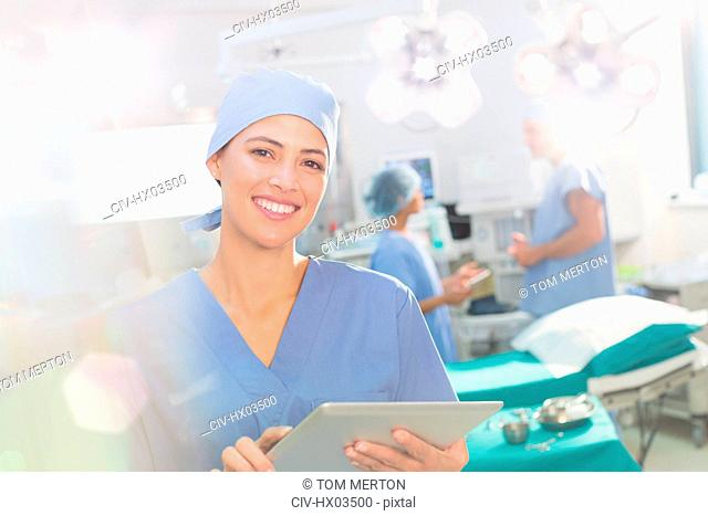 Portrait smiling, confident female surgeon using digital tablet in operating room